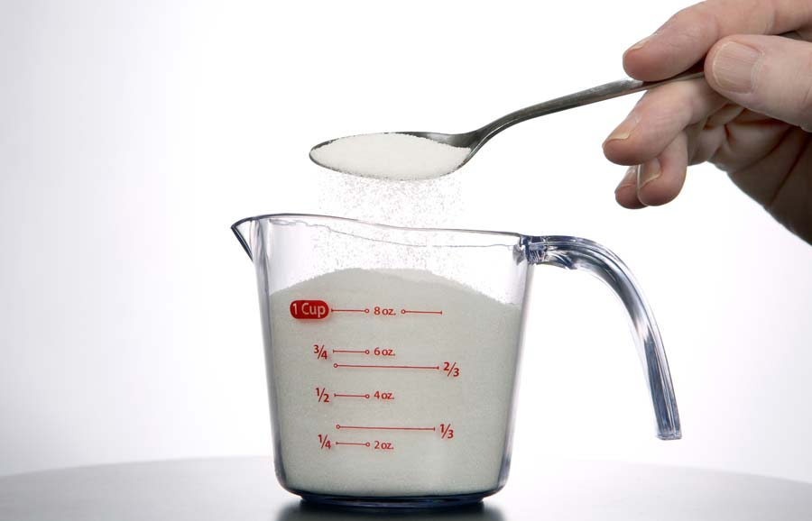 Measuring tablespoons into a cup (cup measurement in glass jug)