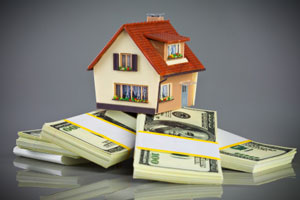 mortgage refinancing, house on piles of bank notes - photo