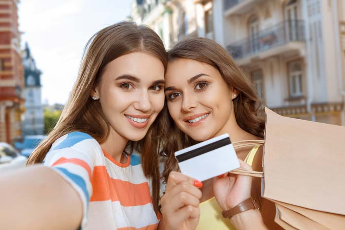 Two young ladies taking a selfie, holding a credit card