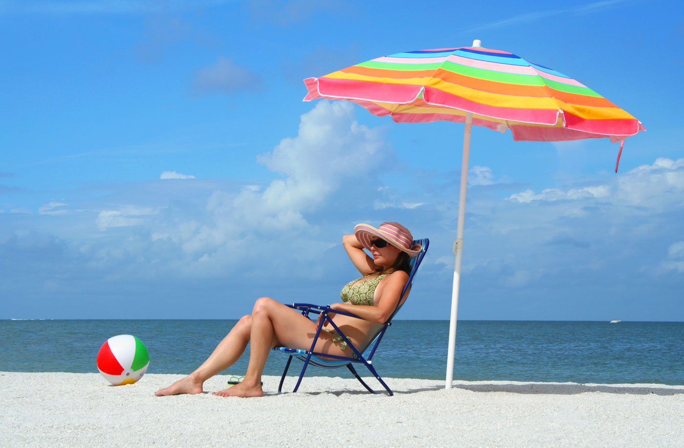Lady sitting under parasol on a sun-kissed beach