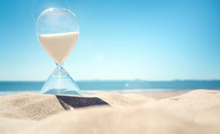 Counting down with hourglass on beach
